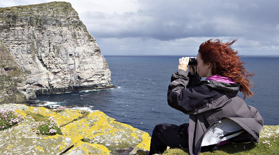 Visitor looking at the seabird colonies at the Noup, Noss NNR, Shetland ©Lorne Gill/SNH. For information on reproduction rights contact the Scottish Natural Heritage Image Library on Tel. 01738 444177 or www.nature.scot