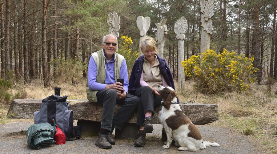 Visitors and their dog resting at a seated area on the visitor centre trail at Beinn Eighe National Nature Reserve. ©Lorne Gill/SNH. For information on reproduction rights contact the Scottish Natural Heritage Image Library on Tel. 01738 44417