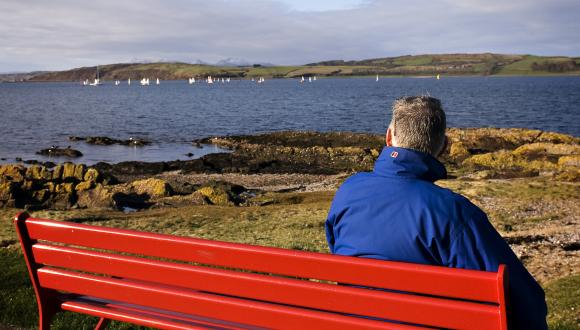 Man in blue jacket sitting on red bench, watching sailing boats on the Firth of Clyde. ©beckyduncanphotographyltd/SN. For information on reproduction rights contact the Scottish Natural Heritage Image Library on Tel. 01738 444177 or www.nature.scot