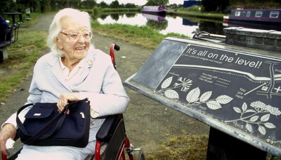 Woman in wheelchair beside sign for 'all ability' paths by canal, Ratho.© George Logan/SNHFor information on reproduction rights contact the Scottish Natural Heritage Image Library on Tel. 01738 444177 or www.nature.scot